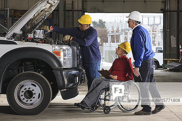 Vehicle mechanic working on a truck and inspectors  including a man in wheelchair  watching him work