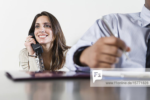 Business man in foreground with business woman using telephone in background.