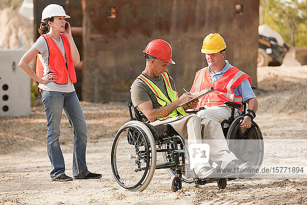 Construction job site with men in wheelchairs and woman talking on the phone