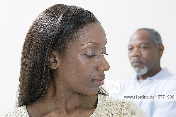 Close-up of a middle-aged woman looking at a middle-aged man behind her