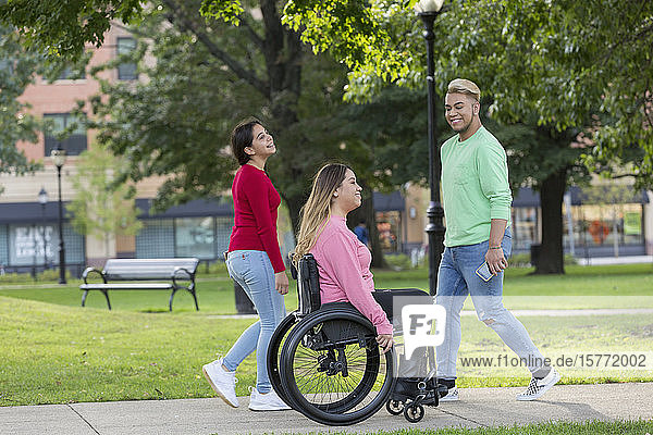 Woman who has Spinal Cord Injury walking with siblings in park
