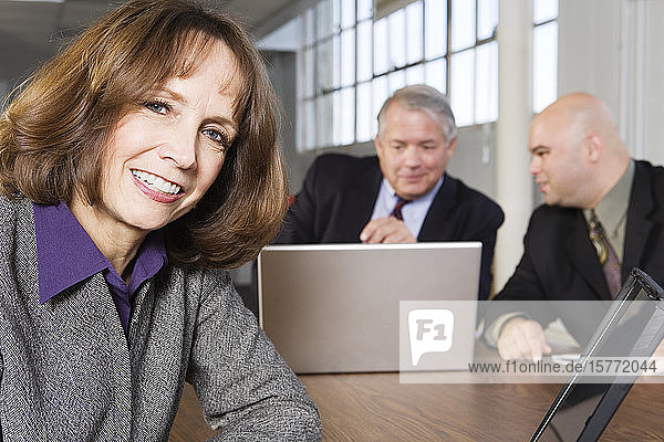 Portrait of a business woman smiling with businessmen working in background.