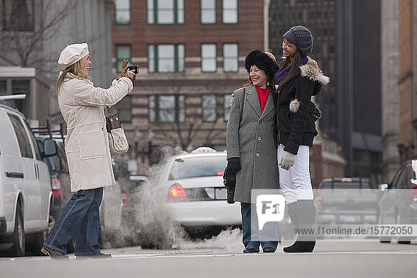 A woman taking a picture of friends on a city street; Boston  Massachusetts  United States of America