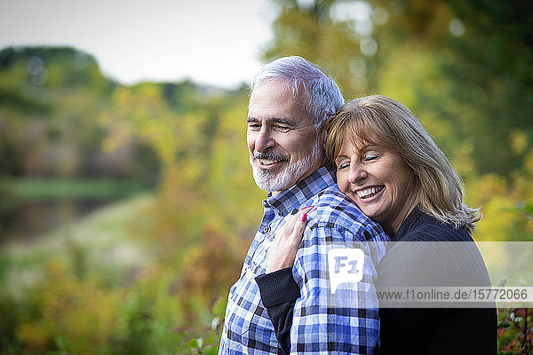 A mature couple enjoying time together and enjoying the sunset along a river in a city park on a warm fall evening; St. Albert  Alberta  Canada