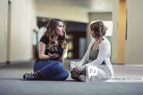 A young woman and her youth leader discussing their faith in a hallway of a church: Edmonton  Alberta  Canada