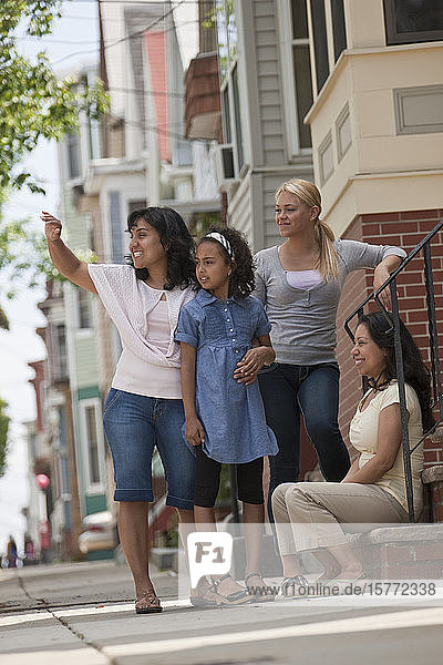 Child greets a woman with an embrace in front of a house as two women stand watching