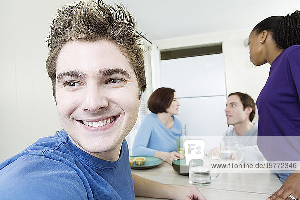 Close up of a young man with friends in background.