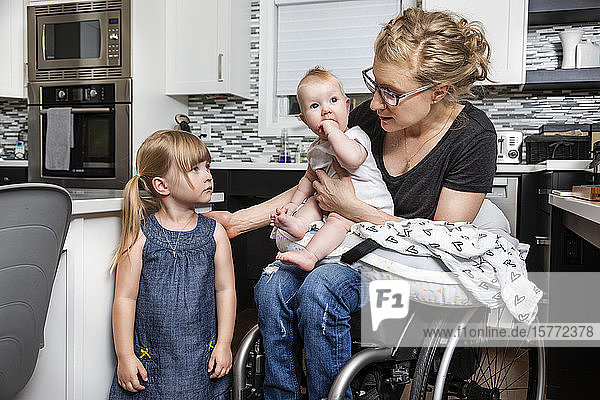 A paraplegic mom in a wheelchair talking with her daughter and holding her baby in her lap while working in her kitchen; Edmonton  Alberta  Canada