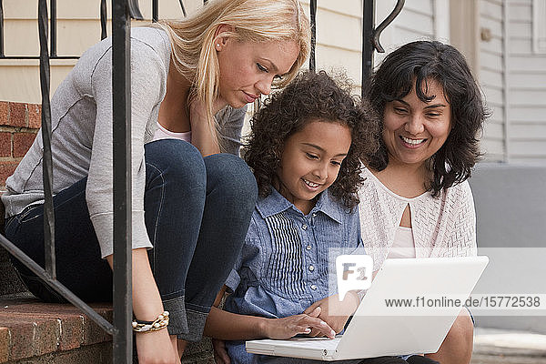 A young girl uses a laptop while her mother and a young woman look on