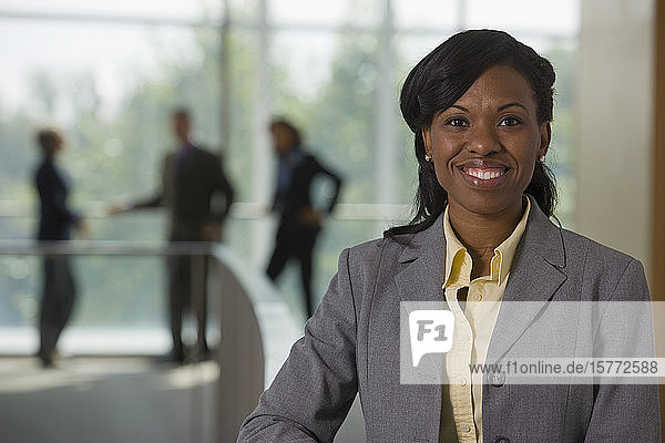 Portrait of business woman with team of business people in the background