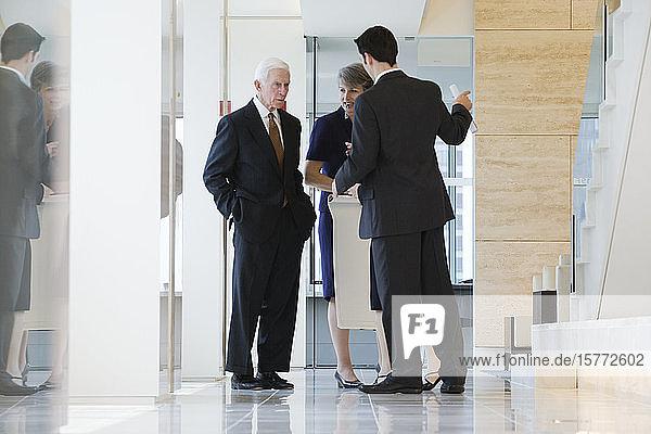 Businesspeople standing in a corridor.