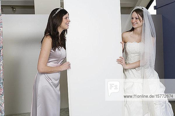 Cheerful bride with bridesmaid.