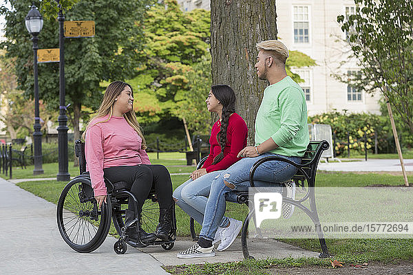 Woman who has Spinal Cord Injury talking with siblings in park