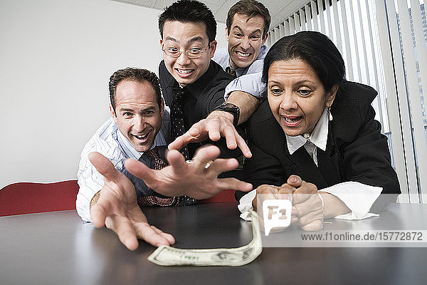 View of businesspeople grabbing a dollar bill.
