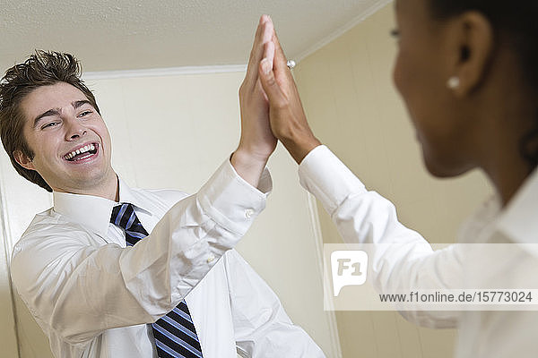 View of a young man and woman doing high five.