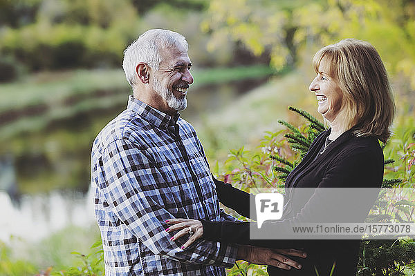 A mature couple enjoying quality time together and stopping to hug  while walking along a river in a city park on a warm fall evening; St. Albert  Alberta  Canada
