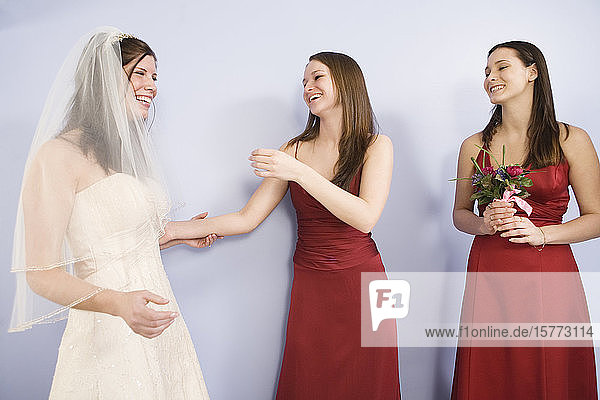 Cheerful young bride standing with bridemaids.