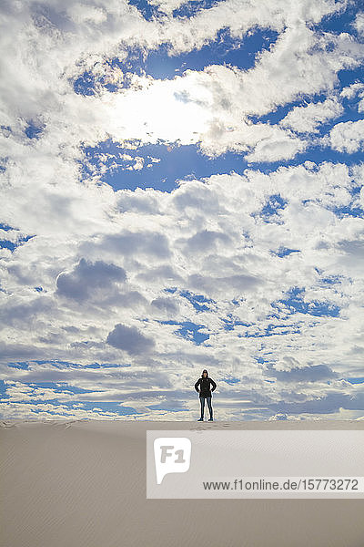 Young woman standing on the white sand with blue sky and cloud  White Sands National Monument; Alamogordo  New Mexico  United States of America