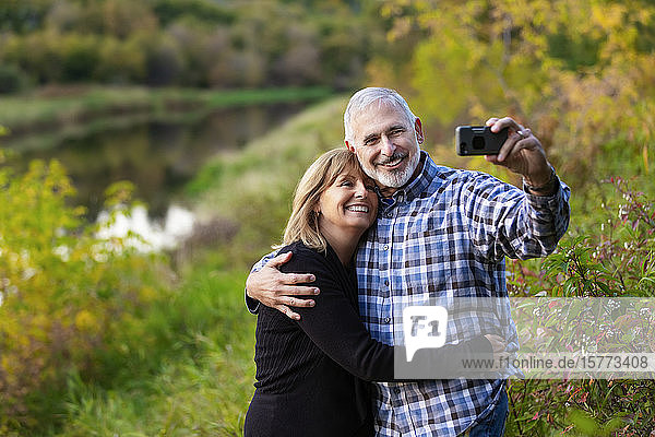 A mature couple enjoying time together and taking a self-portrait while enjoying the sunset along a river in a city park on a warm fall evening; St. Albert  Alberta  Canada