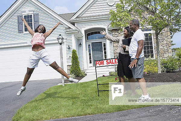 Side profile of a middle-aged man and a real estate agent looking at a middle-aged woman jumping