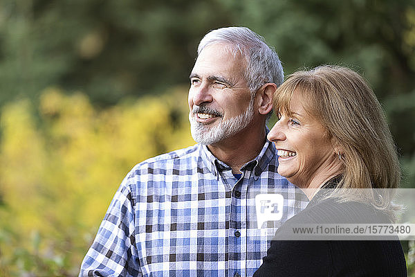 A mature couple enjoying time together and taking in the view in a city park on a warm fall evening; St. Albert  Alberta  Canada