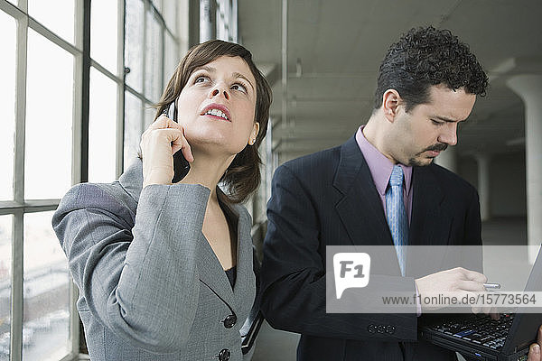 Businesswoman talking on a mobile phone with a businessman using a laptop beside her