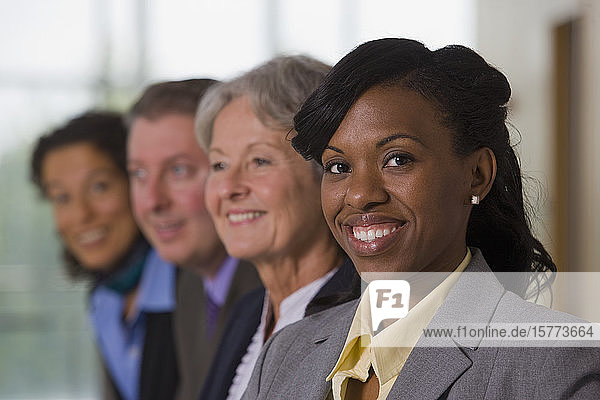 Team of business people with three business women and one business man standing in a row