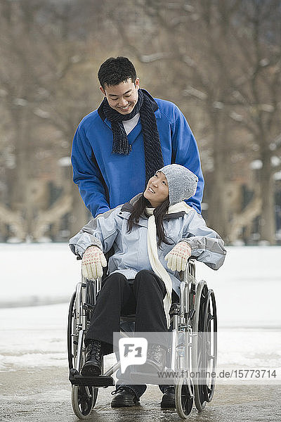Young woman sitting in a wheelchair with a young man standing behind him