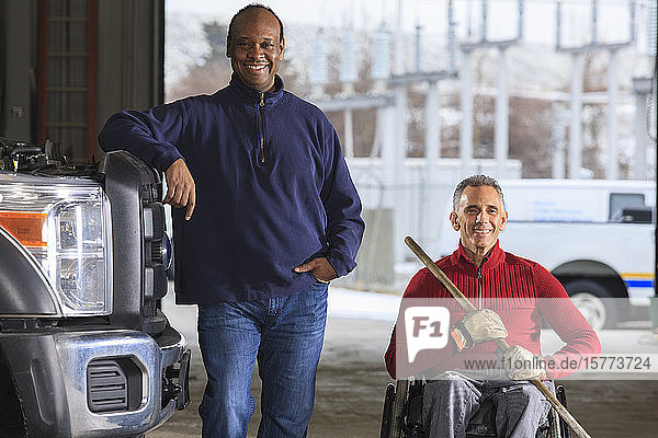 Vehicle mechanic and man in wheelchair with broom posing for a picture