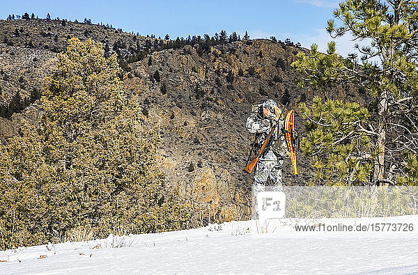 Hunter with camouflage clothing and rifle looking out with binoculars; Denver  Colorado  United States of America
