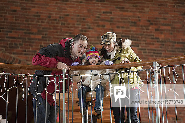 Mother and father sit with young daughter in a downtown shopping area