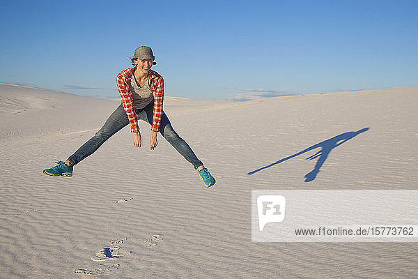 A young woman leaps in the air on the white sand with blue sky  White Sands National Monument; Alamogordo  New Mexico  United States of America