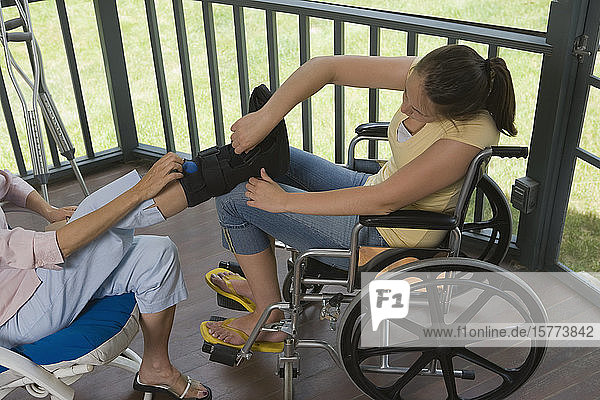 High angle view of a young woman sitting in a wheelchair and adjusting an amputee of her mother