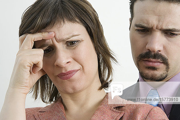 Close-up of a businesswoman suffering from a headache with a businessman behind her