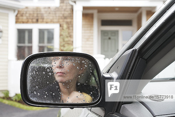 Woman's image reflected on the rearview mirror of a car.