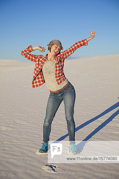 Carefree young woman on the white sand with blue sky  White Sands National Monument; Alamogordo  New Mexico  United States of America