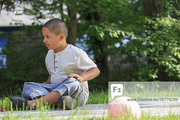 Pre-teen boy outside sitting on the ground with trees in the background