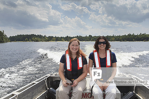 Two women in lifejackets sitting in a motorboat looking at the camera as it travels across a lake