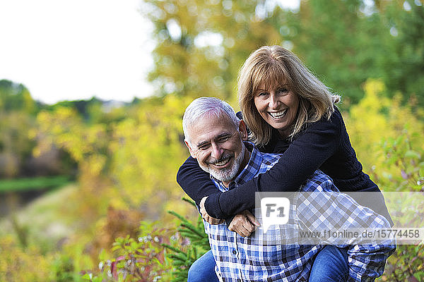 A mature huband having fun and giving his wife a piggy back ride on a path along a river in a city park on a warm fall evening; St. Albert  Alberta  Canada
