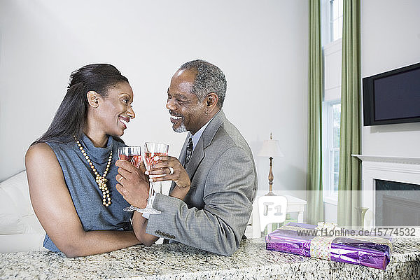 Middle-aged couple toasting with wine glasses and smiling
