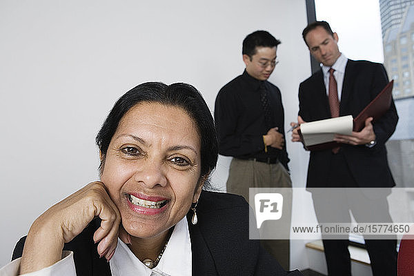 View of a businesswoman smiling with architects discussing.