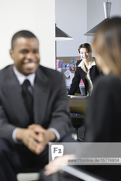 Business woman looking at her colleagues in office.
