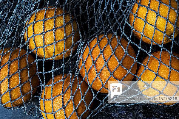 Hochwinkel-Nahaufnahme von Orangen in grauer Netztasche auf schwarzem Hintergrund.