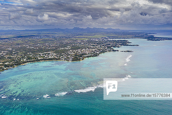 Dramatic sky over coral reef and inland  aerial view by drone Grand Baie (Pereybere)  north-west coast  Mauritius  Indian Ocean  Africa