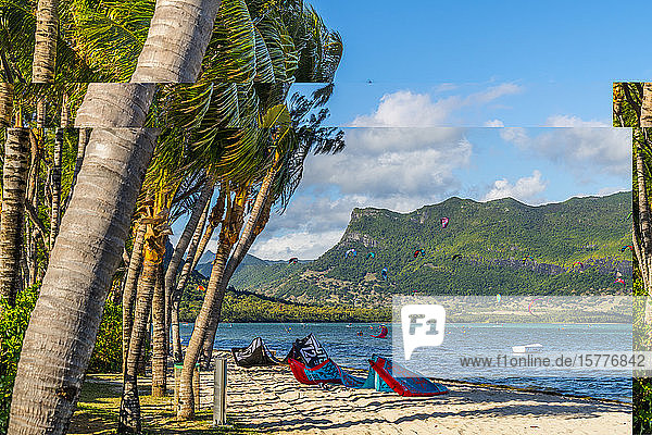 Kitesurf in the ocean seen from tropical palm-fringed beach  Le Morne Brabant  Black River district  Mauritius  Indian Ocean  Africa