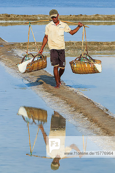 Man with shoulder pole harvesting the salt fields around the Praek Tuek Chhu River estuary south of the city  Kampot  Cambodia  Indochina  Southeast Asia  Asia
