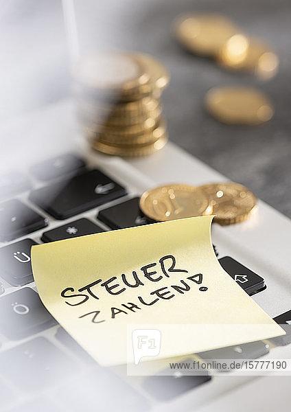 Tastatur und Merkzettel - Steuern zahlen