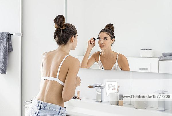 Frau in Badezimmer beim Schminken