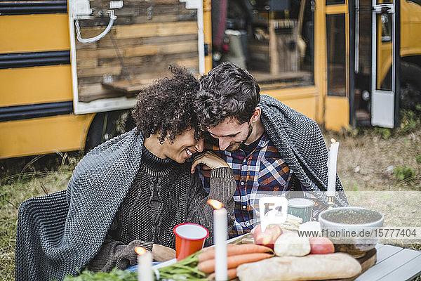 Junges multiethnisches Paar in eine Decke gewickelt  das während des Zeltens gemeinsam seine Freizeit verbringt