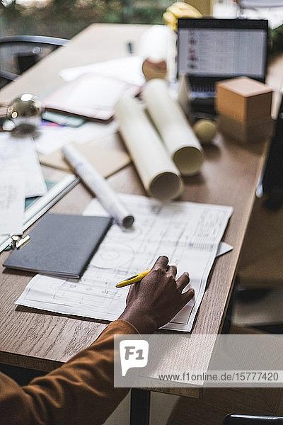 Geschnittene Hand einer Designerin  die am Schreibtisch im Home-Office an einer Blaupause arbeitet